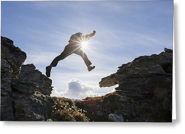 Knapsack Greeting Cards - Backlit View Of Hiker Leaping Between Greeting Card by Scott Dickerson