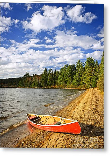 Canoe Greeting Cards - Red canoe on lake shore Greeting Card by Elena Elisseeva