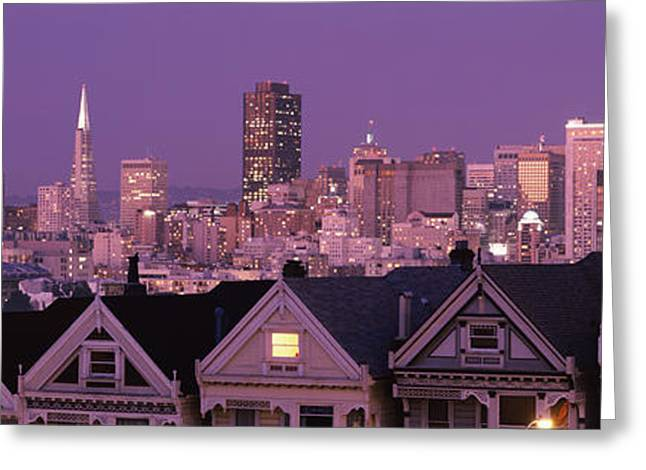 Alamo Square Greeting Cards - Skyscrapers Lit Up At Night In A City Greeting Card by Panoramic Images