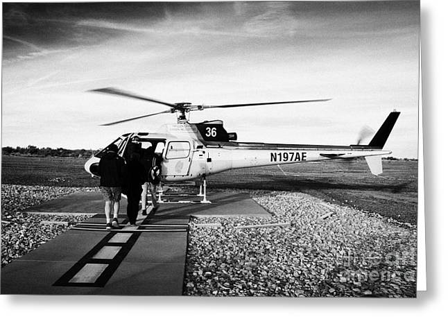 Helipad Greeting Cards - passengers boarding papillon helicopter tours on helipad at Grand canyon west airport Arizona USA Greeting Card by Joe Fox
