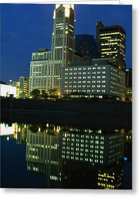 Night Scenes Greeting Cards - Buildings In A City Lit Up At Night Greeting Card by Panoramic Images