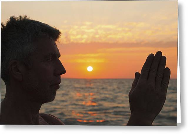 Praying Hands Greeting Cards - A Man In Prayer Or Yoga Pose As The Sun Greeting Card by Debra Brash