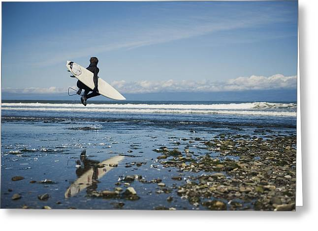 Wave Image Greeting Cards - A Man Walks With His Surfboard Down The Greeting Card by Helene Cyr