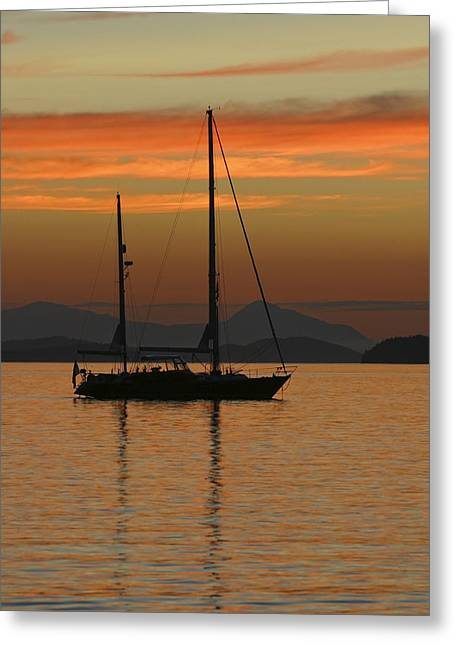Blue Sailboats Greeting Cards - A Sailboat Is Anchored For The Night In Greeting Card by John Delapp