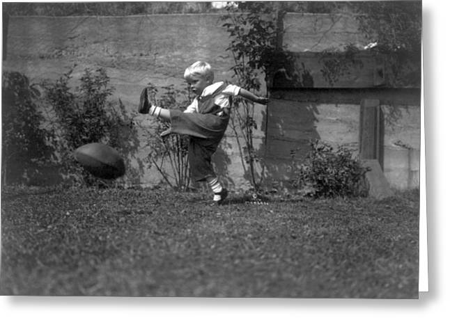 A Small Boy Kicking Football Greeting Card by Underwood Archives