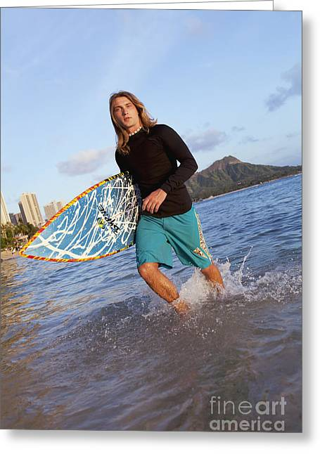 Surf City Greeting Cards - A surfer carrying his surfboard and walking in shallow water_ Waikiki, Oahu, Hawaii, United States of America Greeting Card by Brandon Tabiolo