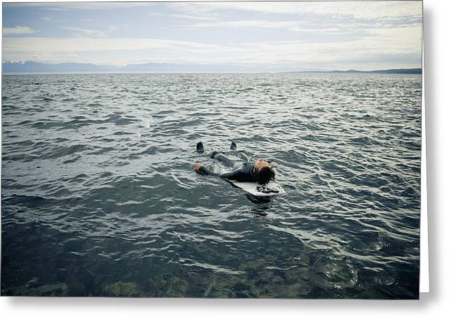 18-19 Years Greeting Cards - A Surfer Lays On His Back On His Greeting Card by Helene Cyr
