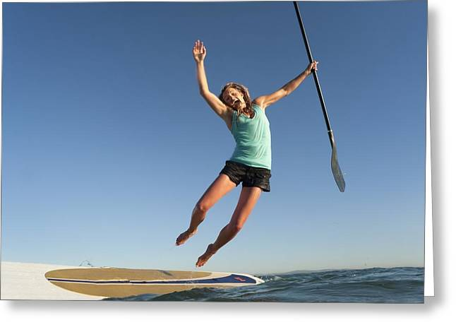 Full-length Portrait Greeting Cards - A Woman Jumps Into The Water Off A Surf Greeting Card by Ben Welsh