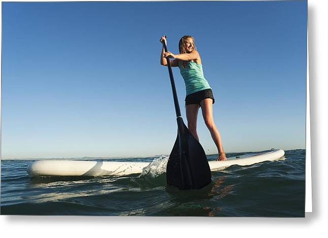 20-29 Years Greeting Cards - A Woman Paddling While Standing On A Greeting Card by Ben Welsh