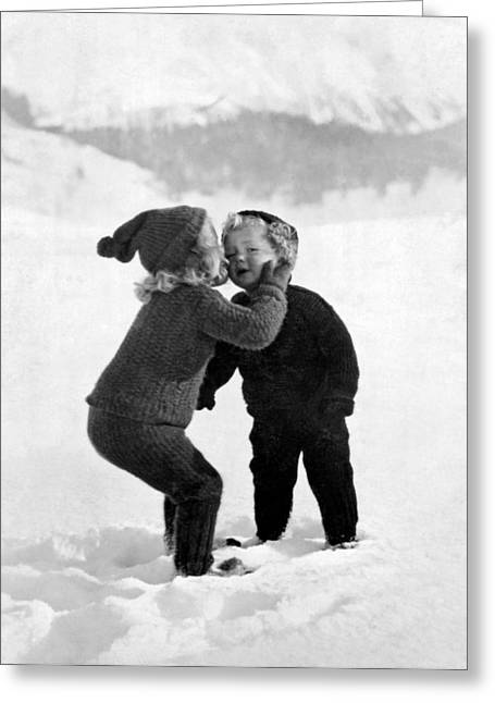 Wintry Photographs Greeting Cards - A young girl gives her little brother a kiss on the cheek in the snow Greeting Card by Unknown Photographer