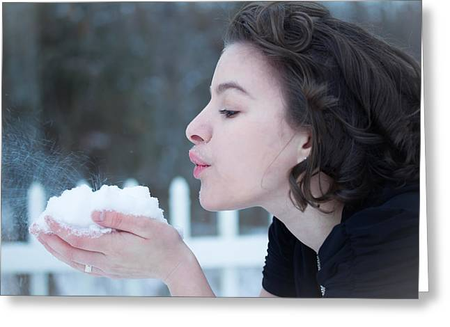 Oxymoron Greeting Cards - A Young Lady Blows Snow Greeting Card by Veda Gonzalez