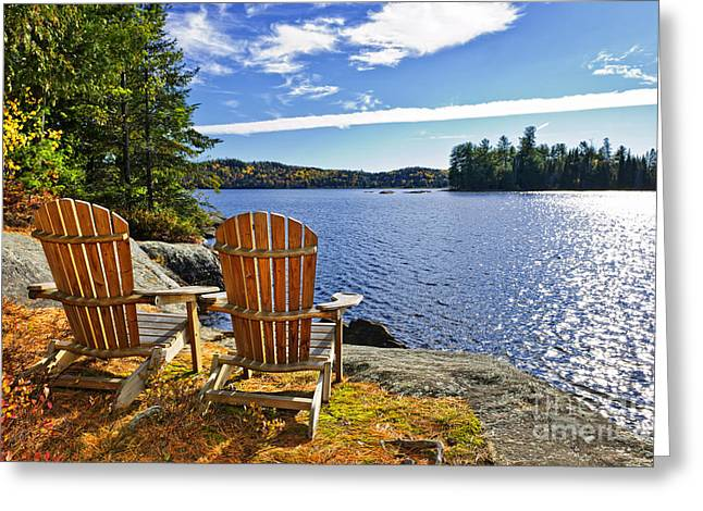 Algonquin Greeting Cards - Adirondack chairs at lake shore Greeting Card by Elena Elisseeva