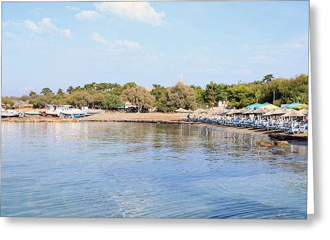 Sunbed Greeting Cards - Aegina town beach and boatyard Greeting Card by Paul Cowan