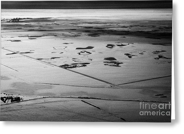Harsh Conditions Photographs Greeting Cards - aerial view of snow covered prairies and remote isolated farmland in Saskatchewan Canada Greeting Card by Joe Fox