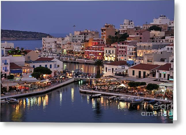 Port Greeting Cards - Agios Nikolaos city during dusk time Greeting Card by George Atsametakis