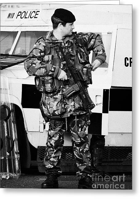 Terrorism Greeting Cards - Armed British soldier at PSNI landrover on crumlin road at ardoyne shops belfast 12th July Greeting Card by Joe Fox