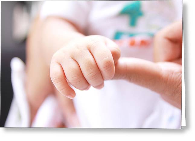 Caring Mother Greeting Cards - Baby hand holding mother finger Greeting Card by Wanchai Yoosumran