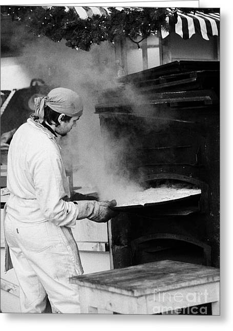 Woodburning Greeting Cards - Baker removing tray of bread from an outdoor wooden baking oven on a stall with steam escaping at the christmas market Berlin Germany Greeting Card by Joe Fox