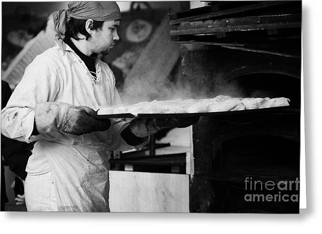 Woodburning Greeting Cards - Baker removing tray of bread with steam rising from an outdoor wooden baking oven on a stall at the christmas market Berlin Germany Greeting Card by Joe Fox
