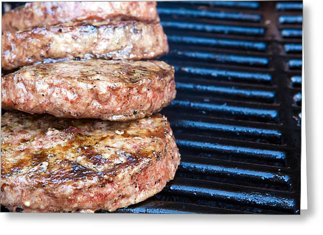 Grate Greeting Cards - Beef quarterpounder burgers begin to cook on the gas barbecue Greeting Card by Fizzy Image