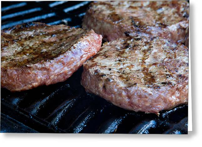 Hamburger Greeting Cards - Beef quarterpounder burgers begin to cook on the gas barbecue Greeting Card by Fizzy Image