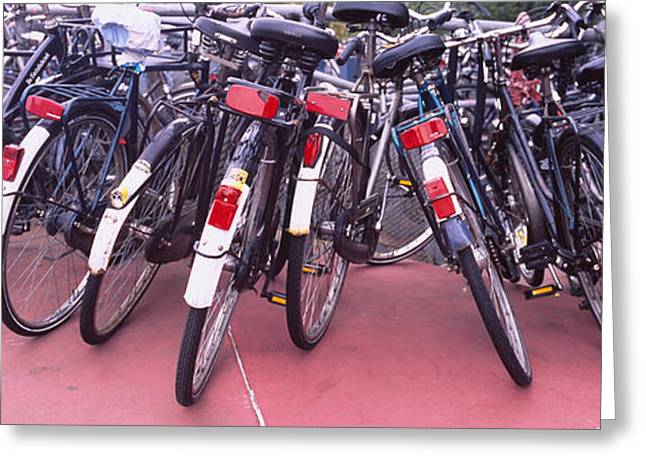 Parking Lots Greeting Cards - Bicycles Parked In A Parking Lot Greeting Card by Panoramic Images