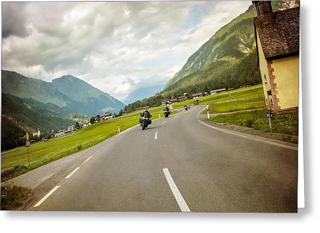 Scenic Drive Greeting Cards - Biker race across mountainous village Greeting Card by Anna Omelchenko