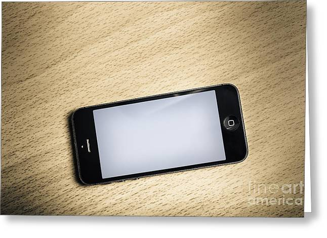 Cellphone Greeting Cards - Blank smart phone on wooden office desk Greeting Card by Ryan Jorgensen