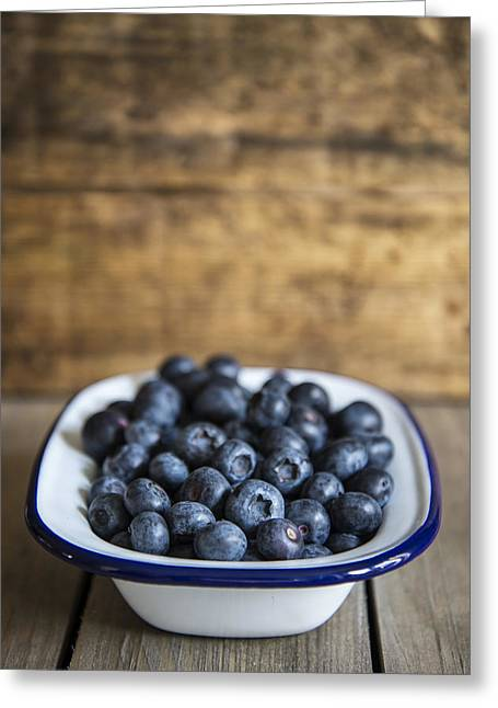 Wooden Bowl Greeting Cards - Blueberries in rustic kitchen setting with old wooden background Greeting Card by Matthew Gibson