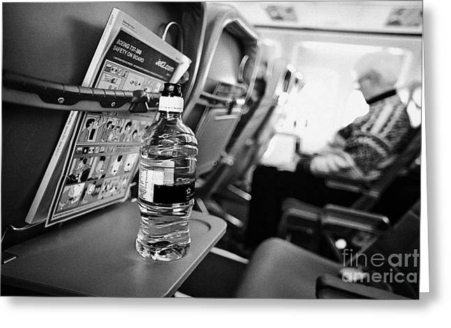 Cabin Interiors Photographs Greeting Cards - Bottle Of Water On Tray Table Interior Of Jet2 Aircraft Passenger Cabin In Flight Greeting Card by Joe Fox