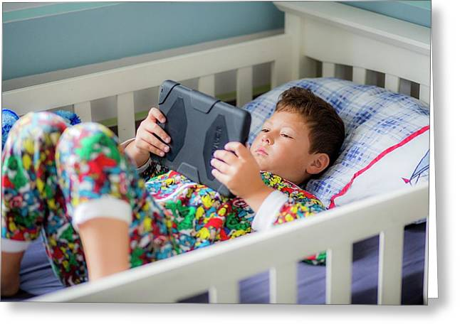 Boy In Bed Using A Digital Tablet Greeting Card by Samuel Ashfield