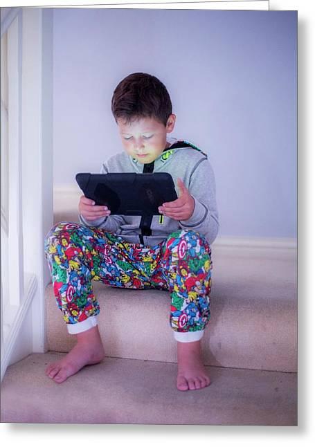 Boy Sitting On A Step Using A Tablet Greeting Card by Samuel Ashfield