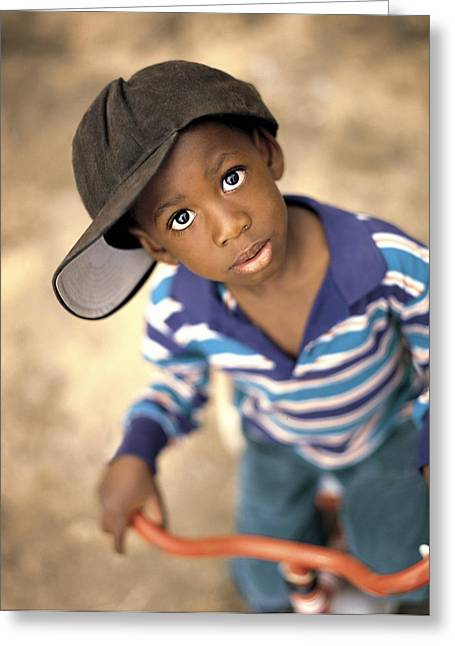 Black Ancestry Greeting Cards - Boy Wearing Over Sized Hat Riding Bike Greeting Card by Ron Nickel