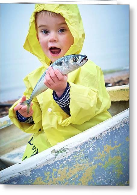 Boy Wearing Raincoat Holding A Mackerel Greeting Card by Ruth Jenkinson