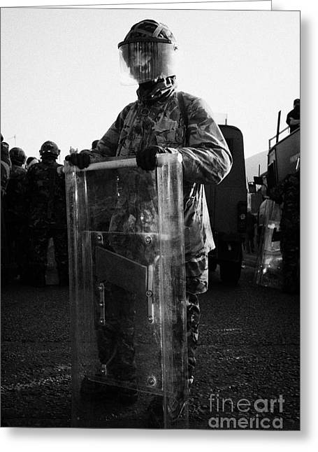 Terrorism Greeting Cards - British Army soldier in riot gear stands guard on crumlin road at ardoyne shops belfast 12th July Greeting Card by Joe Fox