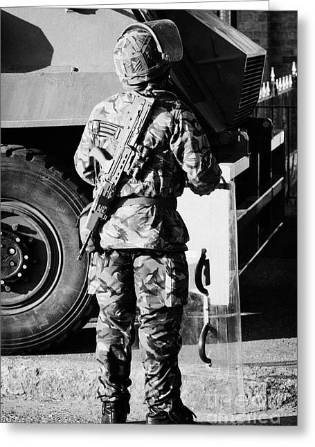 Terrorism Greeting Cards - British army soldier in riot gear with SA80 in front of Saxon vehicle on crumlin road at ardoyne sho Greeting Card by Joe Fox