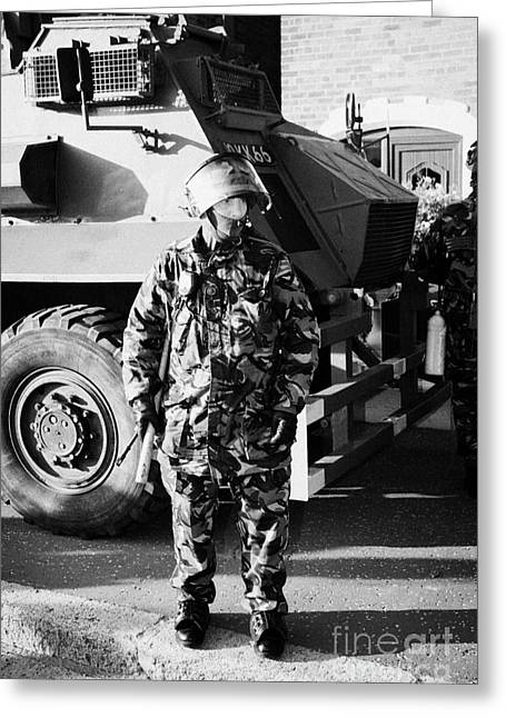 Terrorist Greeting Cards - British army soldier in riot gear with Saxon armoured personnel carrier vehicle on crumlin road at a Greeting Card by Joe Fox