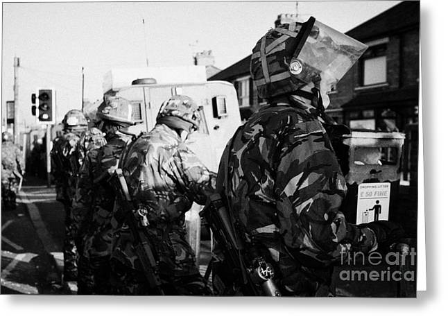 Terrorism Greeting Cards - British Army soldiers in riot gear stand guard on crumlin road at ardoyne shops belfast 12th July Greeting Card by Joe Fox