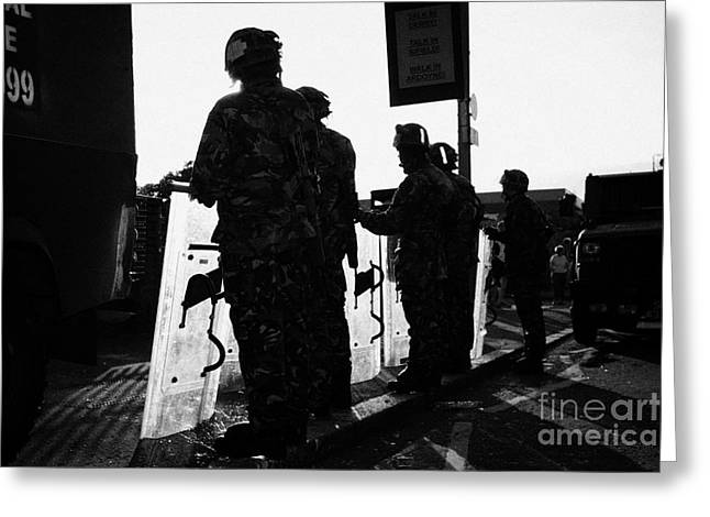 Terrorism Greeting Cards - British army soldiers in riot gear with shields backlit silhouette beneath protest sign on crumlin r Greeting Card by Joe Fox