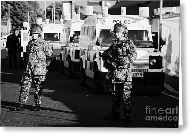 Terrorism Greeting Cards - British army soldiers with PSNI landrovers on crumlin road at ardoyne shops belfast 12th July Greeting Card by Joe Fox