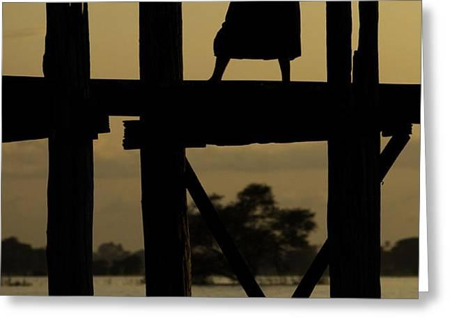 Buddhist monk walking over U Bein's bridge at sunset Greeting Card by Ruben Vicente