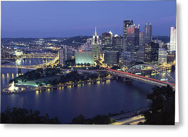 Monongahela River Greeting Cards - Buildings Along A River Lit Up At Dusk Greeting Card by Panoramic Images