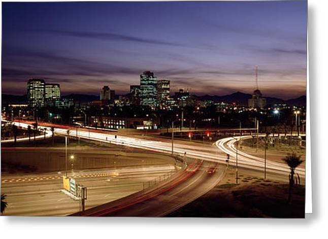 Locations Greeting Cards - Buildings In A City Lit Up At Dusk, 7th Greeting Card by Panoramic Images