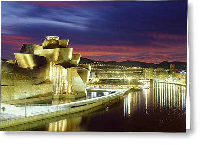 Guggenheim Greeting Cards - Buildings Lit Up At Dusk, Guggenheim Greeting Card by Panoramic Images