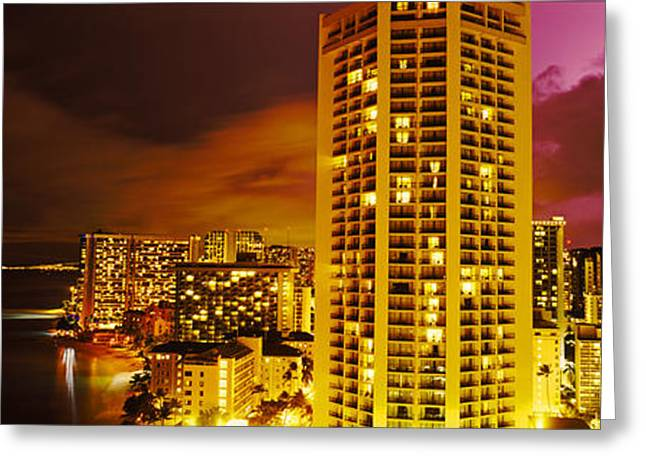 Ocean Photography Greeting Cards - Buildings Lit Up At Night, Honolulu Greeting Card by Panoramic Images