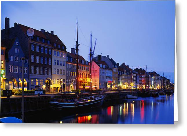 Copenhagen Denmark Greeting Cards - Buildings Lit Up At Night, Nyhavn Greeting Card by Panoramic Images