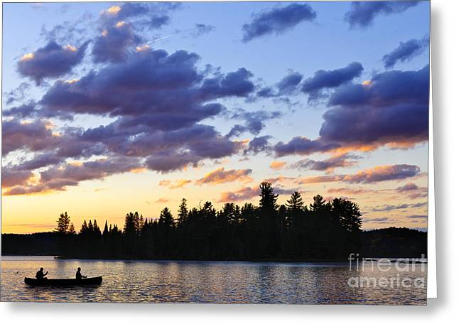 Canoe Greeting Cards - Canoeing at sunset Greeting Card by Elena Elisseeva