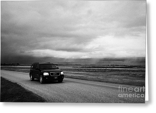 Winter Storm Greeting Cards - car driving on rural road as storm snow clouds forming over the prairies assiniboia Saskatchewan Can Greeting Card by Joe Fox