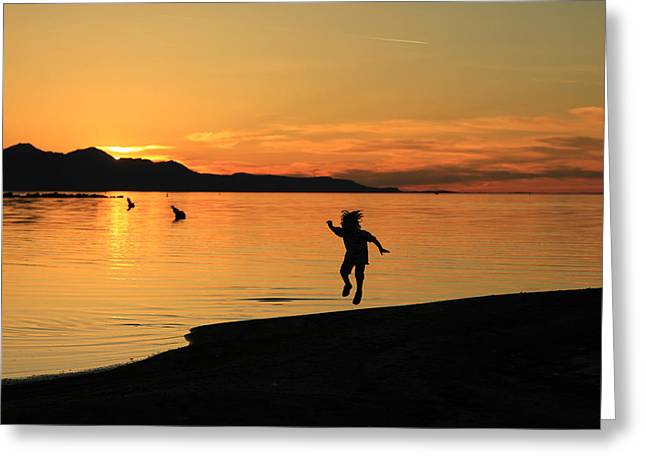 Evening Scenes Greeting Cards - Child playing while the sun sets. Greeting Card by Johnny Adolphson