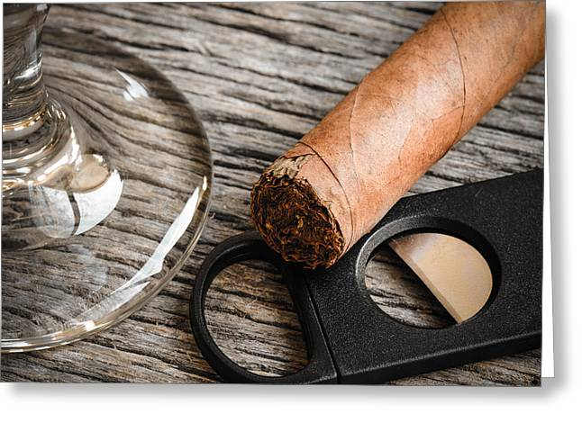 Wood Cutters Greeting Cards - Cigar and Cutter with Glass of Brandy or Whiskey on Wooden Backg Greeting Card by Brandon Bourdages